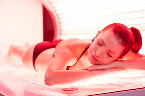 Sunbathing on tanning bed. Beautiful young woman lying on tanning bed and keeping eyes closed